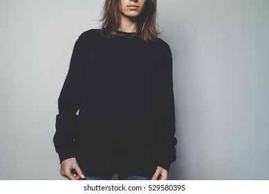Young hipster girl wearing black oversize women?'?s hoodie with blank space for your logo or design, mock-up of black cotton sweatshirt, white wall in the background