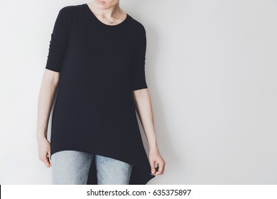 Young hipster girl wearing black oversize t-shirt with blank space for your logo or design, mock-up of black cotton t-shirt, white wall in the background