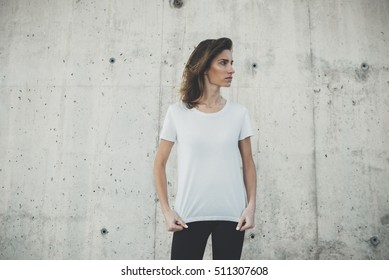 Young hipster girl wearing blank white t-shirt, stone wall background with copy space content or design, mock-up of template t-shirt, attractive woman standing against concrete grey wall background
