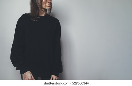 Young hipster girl wearing blank black oversize hoodie with area for your logo or design, mockup of black women's sweatshirt, white wall in the background with copy space for content or text message