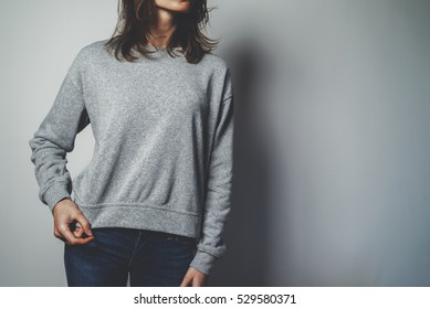 Young hipster girl girl wearing blank cotton sweatshirt with area for your logo, mock-up of grey women'?s hoodie, white wall in the background with copy space for your design or content