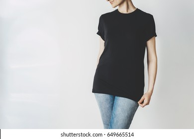 Young hipster girl wearing blue jeans and blank black t-shirt with empty area for your logo or design, mock-up of black long cotton t-shirt