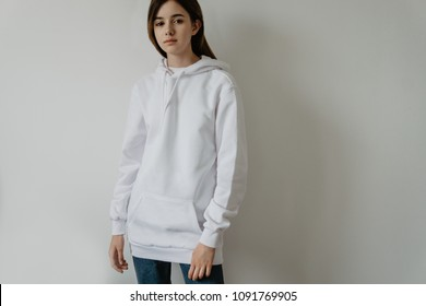 Young hipster girl girl wearing white cotton sweatshirt with area for your logo, mock-up of white women hoodie, white wall in the background with copy space for your design or content
