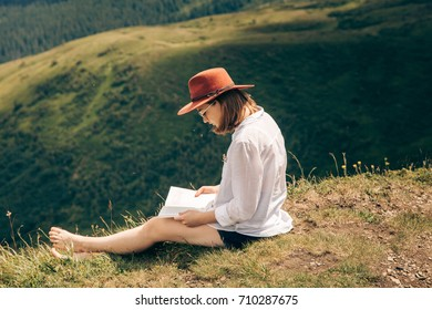 Young hipster girl in white shirt relaxing and reading a book