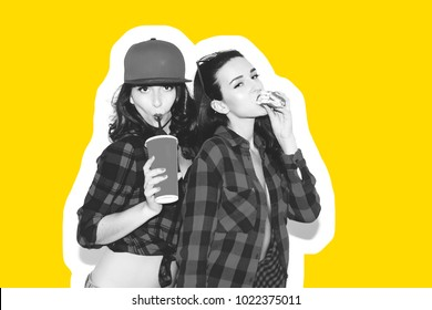 Young hipster girls having fun drinking a soda from straw and holding fast food burger, smile and laugh on the white background.