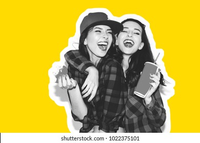 Young hipster girls having fun drinking a soda from straw and holding a burger, smile and laugh on the white background.