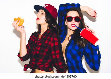 Young hipster girls having fun drinking a soda from straw and holding fast food burger, smile and laugh on the white background. Two young woman urban life concept.