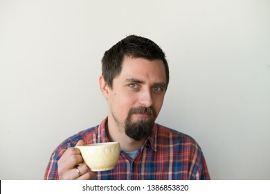 Young hipster in glasses with cup of coffee writing sms on smartphone.