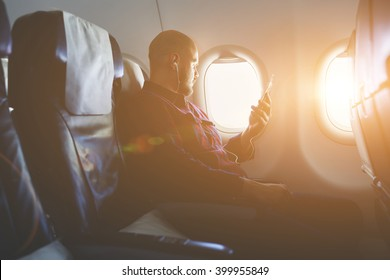 Young hipster guy is enjoying music in headphones via cell telephone and looking at window, while is sitting in plane. Businessman is listening audio book via mobile phone during flying in an airplane