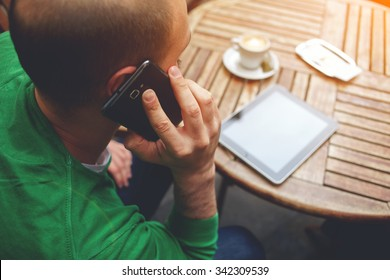 Young hipster guy having having conversation on mobile phone while sitting at the table with touch pad, man talking on cell telephone while rest after work on digital tablet with copy space screen