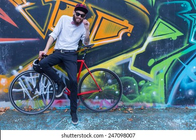 Young hipster guy with his bicycle posing.