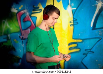 young hipster guy listening to music on red headphones and stares at his smart phone on a graffiti background