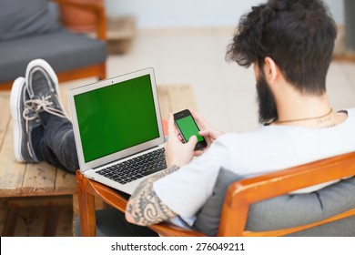 young hipster guy using a laptop and a smart phone.focus on the phone