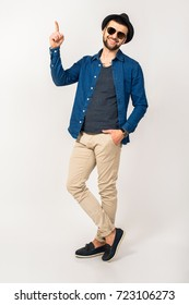 young hipster handsome stylish man isolated on white studio background, denim shirt, trousers, hat, sunglasses, standing, full height, pointing finger, smiling, happy