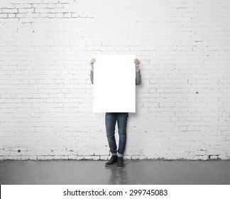 young hipster holding poster in brick room