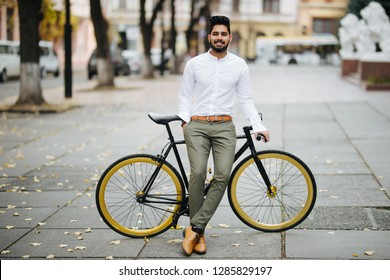 A young hipster indian man posing next to his bicycle.