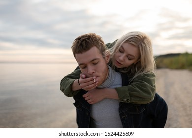Young hipster inhaling smoke from marijuana joint with closed eyes while carrying blond girlfriend on back on lake coast in evening
