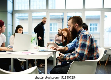 Young hipster male architect working with laptop computer while his colleagues discussing new successful startup project. Spanish student man searching information in internet to prepare for exams