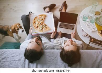 Junge Hipster, männlich und weiblich, die zu Hause Pizza mit Laptop und Hund essen