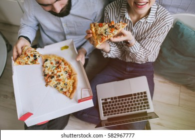 Young hipster male and female couple home eating pizza with laptop
