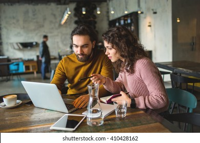 Young hipster male and female working with laptop together in trendy cafe