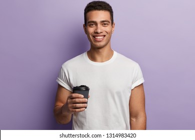 Young hipster male with toothy smile, enjoys free time, wears casual white t shirt, holds takeaway coffee, isolated over purple background, drinks hor beverage after lunch. People and leisure