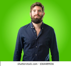 Young hipster man with big beard puffing out cheeks, having fun making funny face over green background