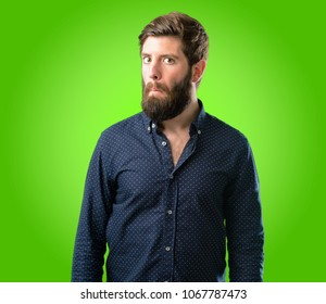 Young hipster man with big beard having skeptical and dissatisfied look expressing Distrust, skepticism and doubt over green background