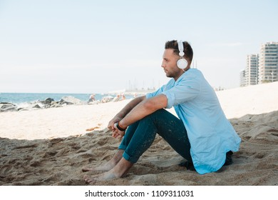 Young hipster man in a blue shirt and jeans listening to music in headphones on a smartphone and is sitting on beach sand looking at sea. Digital Music lounge and relaxing concept