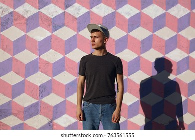 Young hipster man in cap standing and looking away on background of painted wall.