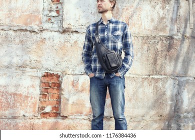 Young hipster man in casual wear with stylish leather crossbody bag standing against concrete wall. Modern city lifestyle.