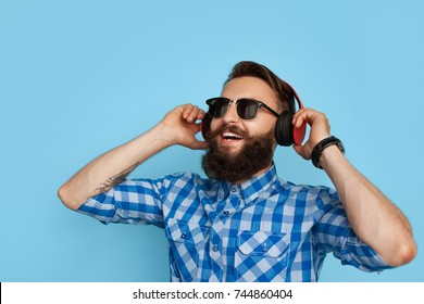 Young hipster man in checkered shirt and sunglasses wearing earphones looking happy on blue background.