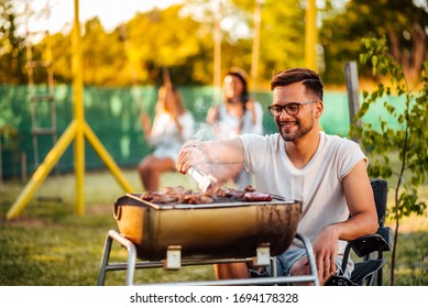 Young hipster man cooking meat on a barbecue grill outdoors on a sunny day.