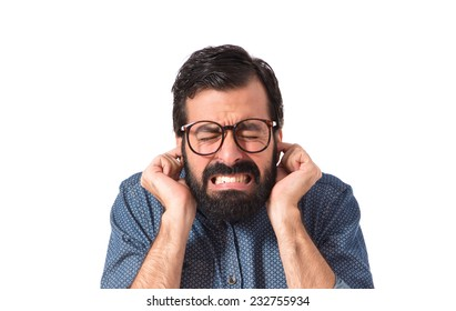 Young hipster man covering his ears