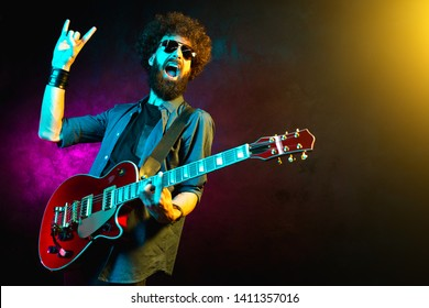 Young hipster man with curly hair with red guitar show rock gesture in neon lights. Rock musician is playing electrical guitar