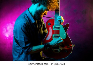 Young hipster man with curly hair with red guitar in neon lights. Rock musician is playing electrical guitar