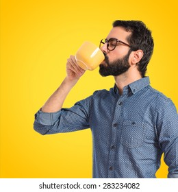 Young hipster man drinking coffee over colorful background