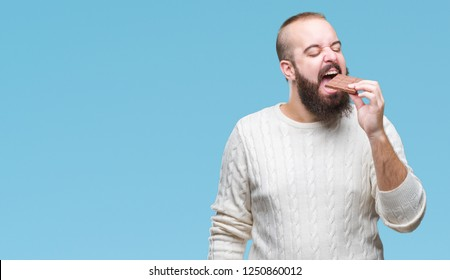 Young hipster man eating chocolate bar over isolated background with a confident expression on smart face thinking serious