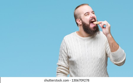 Young hipster man eating chocolate chips cookie over isolated background with a confident expression on smart face thinking serious