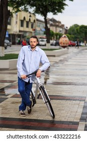 young hipster man with fixed gear bike on city street