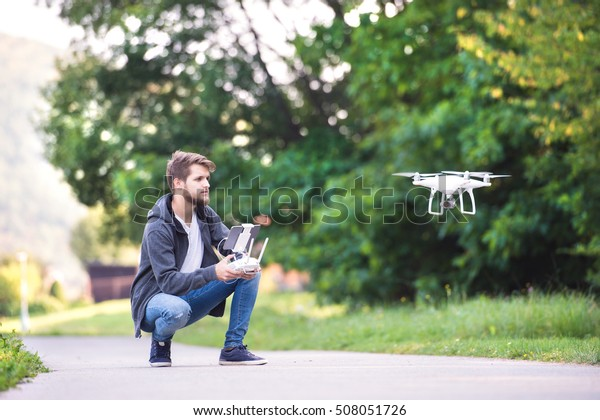 Junge Hip-Mann mit fliegender Drohne. Sonnige grüne Natur.