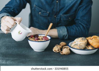 young hipster man having a breakfast on dark table