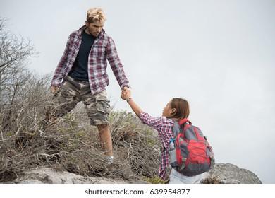 Young hipster man helping woman climbing mountain.