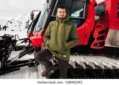 young hipster man hiking in mountains, winter vacation traveling, north, snow, warm clothes, anorak, jeans, boots, snowcat