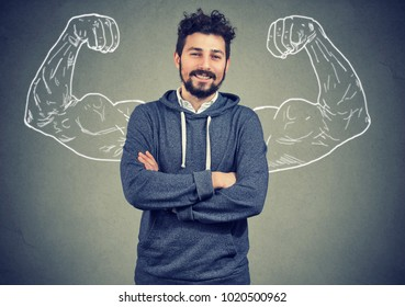 Young hipster man in hoodie standing with painted strong arms on gray background.