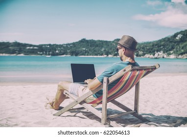 Young hipster man with laptop on tropical beach. Travel, vacation, internet, freelance job concept