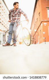 Young hipster man leaning on fixie on street before sunset