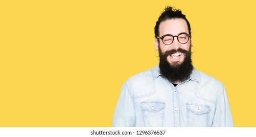 Young hipster man with long hair and beard wearing glasses winking looking at the camera with sexy expression, cheerful and happy face.