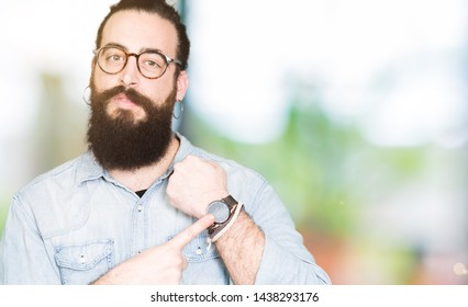 Young hipster man with long hair and beard wearing glasses In hurry pointing to watch time, impatience, upset and angry for deadline delay