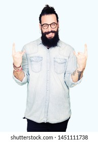 Young hipster man with long hair and beard wearing glasses shouting with crazy expression doing rock symbol with hands up. Music star. Heavy concept.